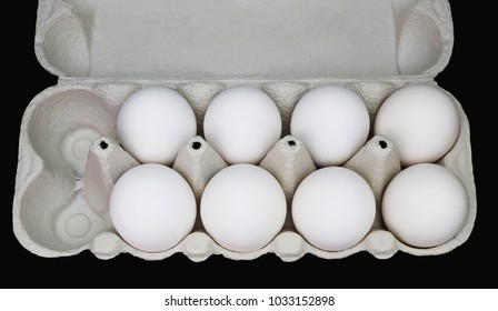 Partly empty grey carton eggbox with several white eggs of perfect shape