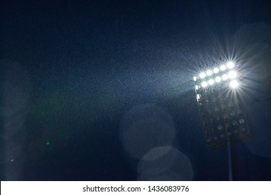 Partly lit floodlighting shining beams of light through the rain, into the darkness of the evening. Bokeh effect.