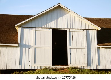 Partly open white barn doors.