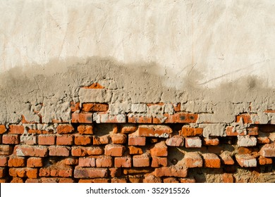 Partly plastered old brick wall with damped plaster,