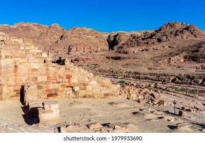 Partly reconstructed wall of the temple of winged lions, with tombs in background at archaeological historic site of Petra, Jordan