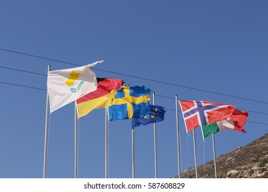 Partly torn, fluttering national flags (respectively, Cyprus, Germany, Sweden, European Union, Norway, Italy) in Falassarna Beach in western part of Crete Island, Greece.