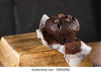 Partly unwrapped chocolate chunks muffin on dark wood and black background