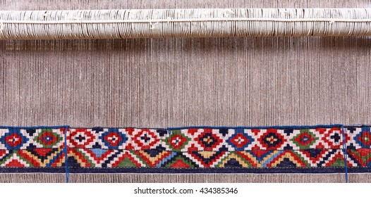 Partly woven carpet, rug on a loom shows wool pile, foundation, warp and weft. Wool is dyed with natural vegetable dyes to create vibrant look.