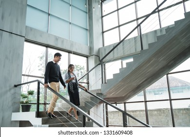 partner of business walking down with chatting on stairs in the office building