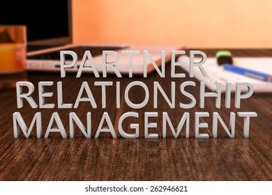 Partner Relationship Management - letters on wooden desk with laptop computer and a notebook. 3d render illustration.