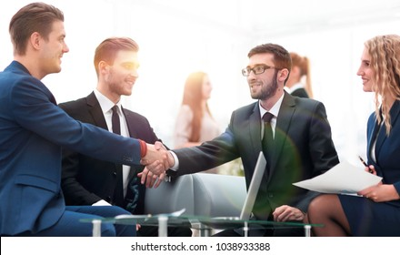 Partners concluding deal and shaking hands in the presence of team members