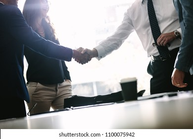 Partners concluding deal and shaking hands in the presence of team members. Businessmen shaking hands in board room and finishing up a meeting.