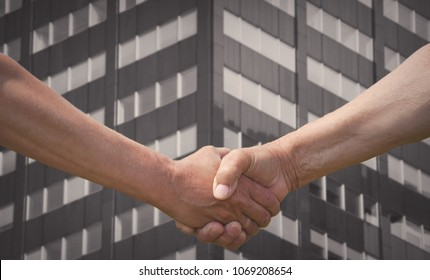 partners hands handshake with building on background