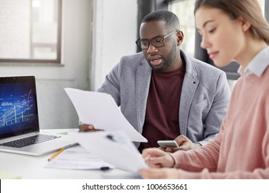 Partners meet to close bargain, have attentive look at contract. Successful female and male invloved in business, study basic document with serious expressions. Team work and collaboration concept