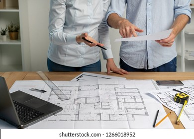 Partners partnership concept. Cropped two designer person in formal wear shirt at workstation table with measurement compass blueprint hold pencil in hand indicate on paperwork graphic paper scheme