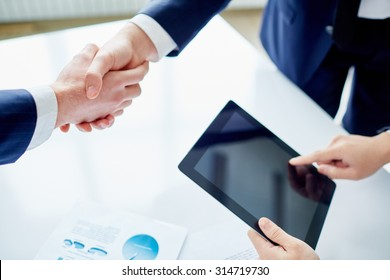 Partners shaking hands while businessman with touchpad networking near by