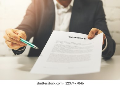 partnership - businessman giving business contract to sign
