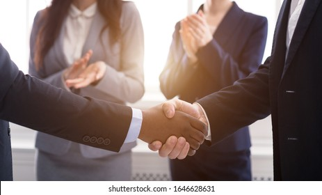 Partnership Concept. Multicultural men shaking hands after sealing the deal, women clapping in the background