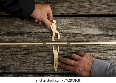 Partnership concept using paper cut outs of men with one holding up a bridge in a gap so that the other can walk across over rustic wooden background.