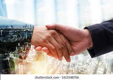 Partnership. double exposure image of investor business man handshake with partner for successful meeting deal with during sunrise and cityscape background, investment, partnership, teamwork concept