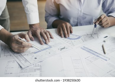 The partnership engineering man or co-workers working on a project and discussing together with looking at blueprint paperwork.