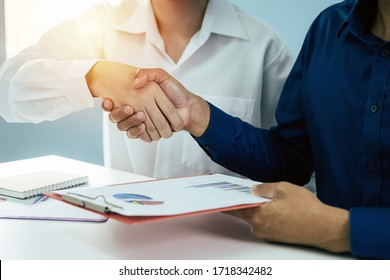 Partnership. group business investor people partner handshake after finishing up business meeting with financial statistics report on desk in office, negotiation, investment and financial concept