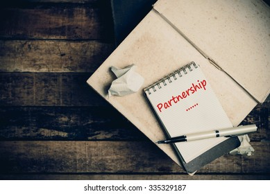 Partnership word on pages sketch book on wood table vertical