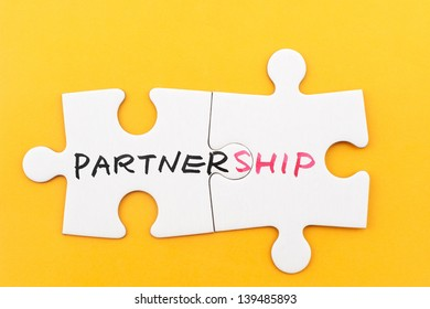 Partnership word written on two pieces of white paper jigsaw puzzles