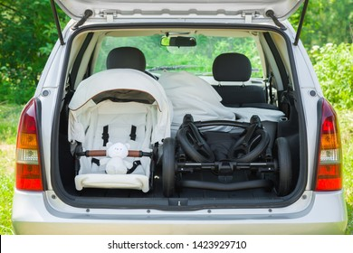 Parts of baby carriage in opened car trunk. Preparing to become parent for future child. Things transportation. Green outdoor nature and sunny summer day atmosphere.