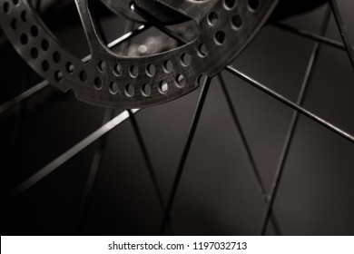 Parts of bicycles rear wheel - breaking disc, chain, spokes.