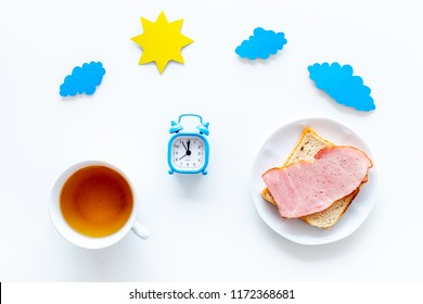 Parts of day. Morning. Time for breakfast. Tea, sandwich near alarm clock, sun and clouds cutout on white background top view