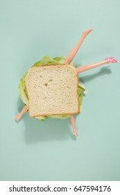 Parts of a doll's body in a sandwich with salad and soft bread on a minimal background color.