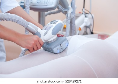 Parts of female body in special white suit having anti cellulite massage with spa apparatus