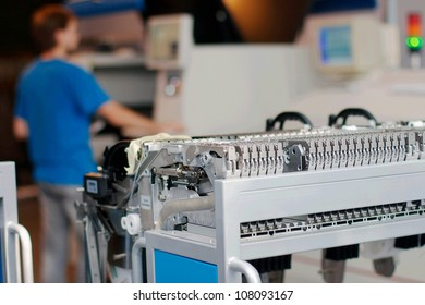 Parts of a machine that produces microchips with worker on a background