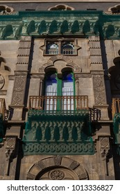 Parts of the Neo-moorish facade of a building in Catania covered by green netting