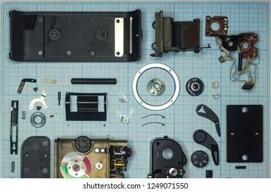 parts old retro film SLR camera on graph paper