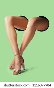 Parts of woman's body - hand, leg stick out of background. Concept of leather goods over complimentary color background.