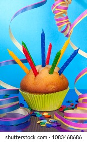 Party accessories with streamers and cupcake against blue background