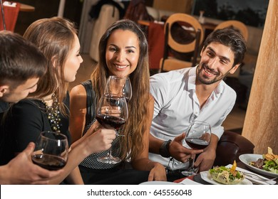 Party after work. Smiling happy friends having a nice dinner with wine in a restaurant.