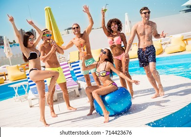 Party all day! Go crazy non stop. Six excited multi national tourists are enjoying at the pool sunny beach disco, with drinks, splashes of water all around! Brunette sit on big ribbon blue ballon
