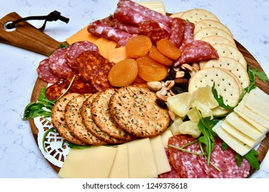 Party appetizer plate consisting of cheese, crackers, nuts, and other party snacks.