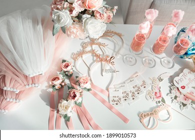 Party attributes in the style of the bride's bachelorette party: bouquet, flower headbands, glasses, plates, veil, stickers.