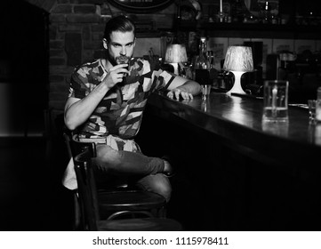 Party and beverage drinking concept. Guy sits at bar counter with glasses of alcohol. Man with beard drinks alcohol on blurred bar background. Macho has rest in bar and drinks shot and liqueur.