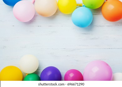 Party or birthday banner with colorful balloons on blue wooden background top view. Flat lay style.