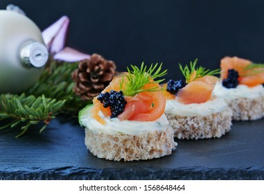 Party canapes with smoked salmon and caviar, closeup on black slate platter on the Christmas table, over dark background