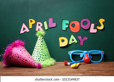 "Party caps, glasses and horns on table near chalkboard with phrase ""April fool's day"""