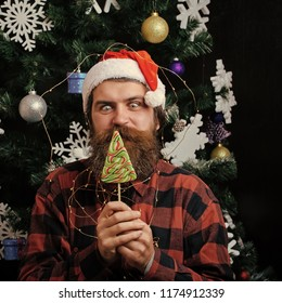 Party celebration and blowjob. santa claus man in hat at decoration. Christmas man with beard on happy face and lollipop. Winter holiday and xmas. New year guy lick candy or sweet.