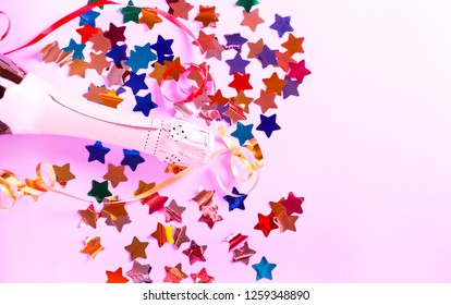 Party and celebration concept - bottle of Champaign and confetti over purple background