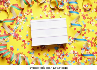 party celebration flat lay with blank light box sign confetti and streamers on yellow background