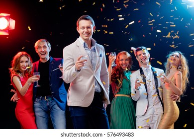 Party and celebration. Group of six happy smiling friends having fun together among confetti in night club.
