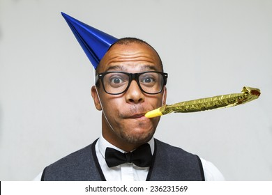 Celebração de festa com este jovem nerd com um chapéu e ventilador de festas. Conceito de Natal, escritório ou aniversário