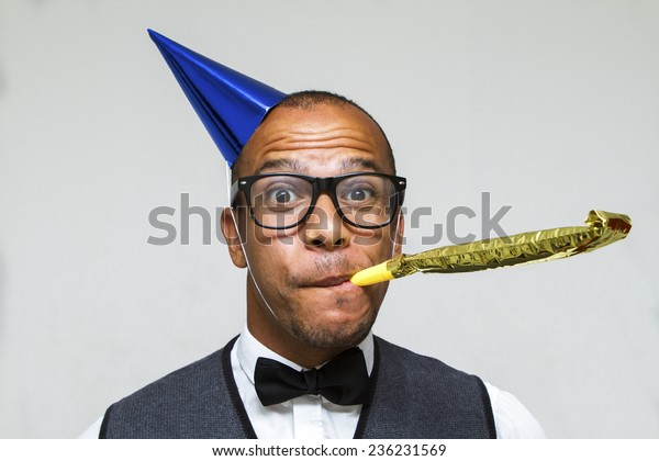Party celebration with this young geek with a hat and party blower. Christmas, office or birthday concept