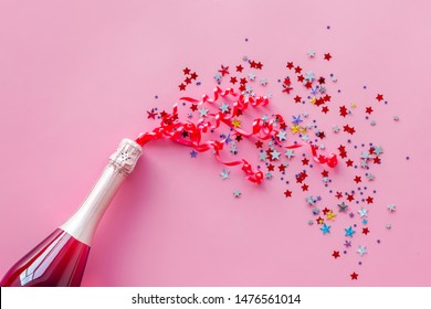 Party with champagne bottle and colorful party streamers on pink background top view