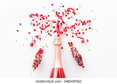Party with champagne bottle, glasses and colorful party streamers on white background top view
